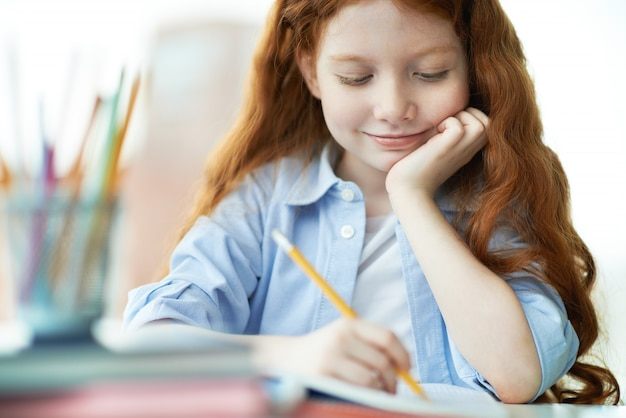 Smiling girl finishing her homework Free Photo