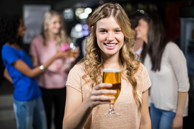 Smiling girl having a beer with her friends Premium Photo