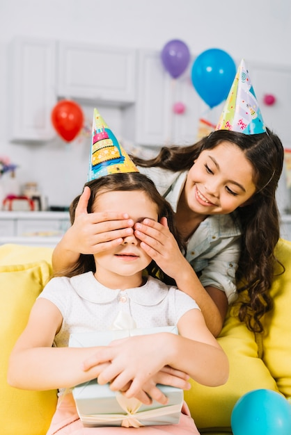 Smiling girl hiding her friend's eyes holding gift box in her hand Free Photo