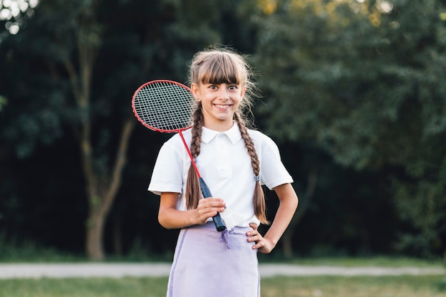 Smiling girl holding badminton standing in the park Free Photo