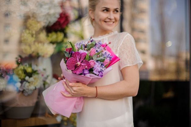Smiling girl holding a bouquet of crimson orchid and violet hyacinth Premium Photo