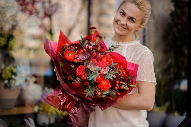Smiling girl holding a bouquet of crimson red flowers Premium Photo