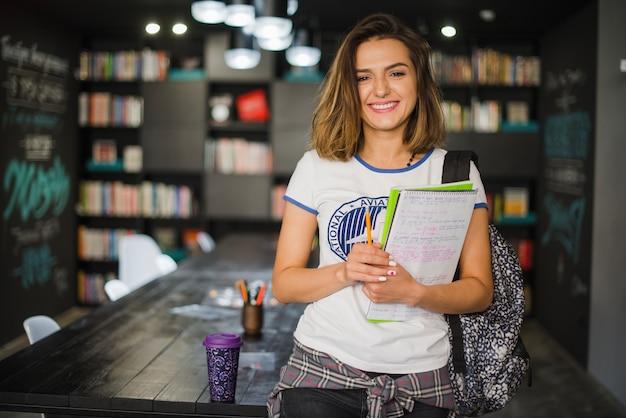 テーブルに傾いているノートを持っている笑顔の女の子 Premium写真