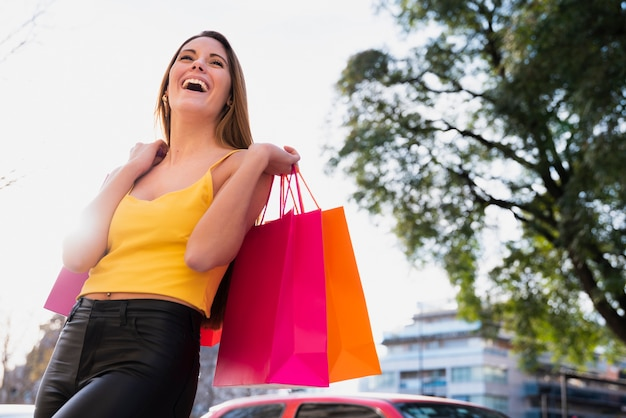 Smiling girl holding shopping bags with tree behind Free Photo