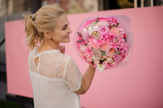 Smiling girl holding a spring bouquet of tender pink and white flowers Premium Photo