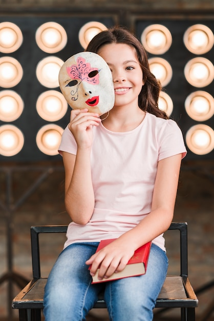 Smiling girl holding venetian mask in her hands Free Photo