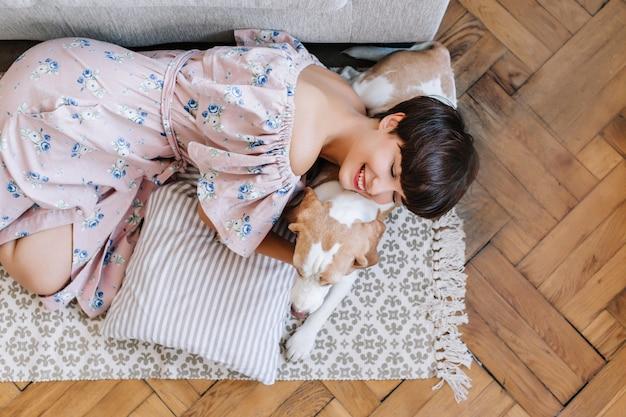 美しいロングドレスの笑顔の女の子は目を閉じてビーグル犬に横たわっています。彼女のペットと一緒にカーペットの上で冷やしている魅力的な笑っている女性の上からの肖像画 無料写真