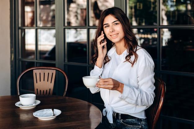 白いシャツで微笑んでいる女の子がカフェでカップと会談を保持 Premium写真