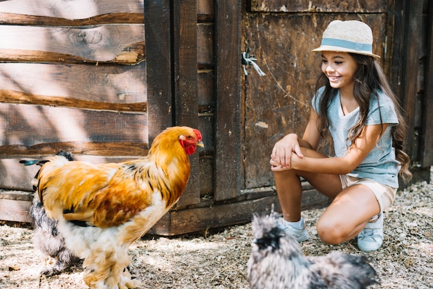 Smiling girl looking at chickens in the farm Free Photo