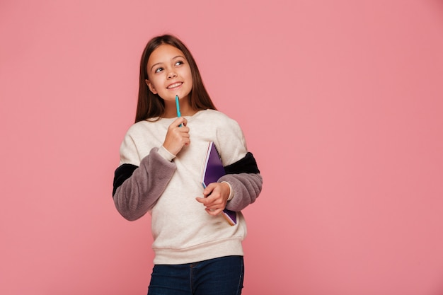 Smiling girl looking up and thinking while holding pencil and books Free Photo
