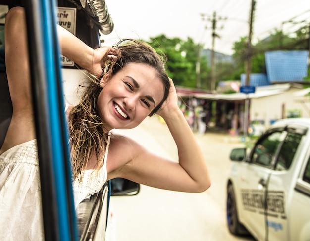 Улыбающаяся девушка смотрит в окно такси, тук-тук Бесплатные Фотографии