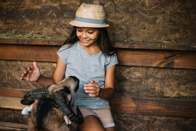 Smiling girl loving sheep in the barn Free Photo