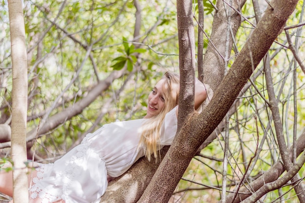 Smiling girl lying on a tree Free Photo