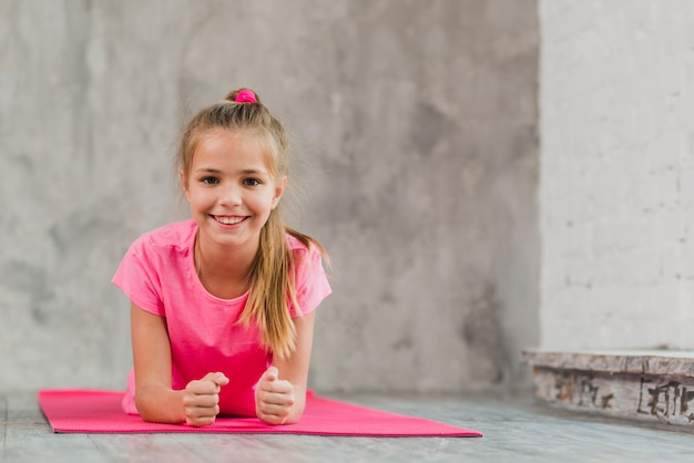 Smiling girl lying on pink exercise mat against concrete backdrop Free Photo