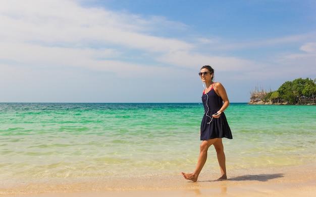Улыбающаяся девушка в синем платье слушает музыку во время прогулки по берегу и держит мобильный телефон, подключенный к наушникам, на острове ко пханган, таиланд Premium Фотографии