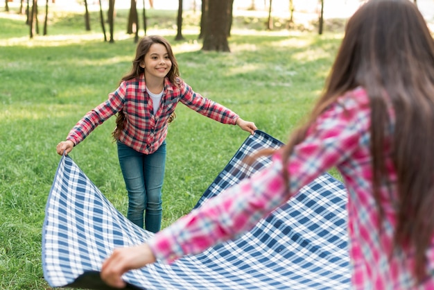 Smiling girl placing blanket on grass with her mother Free Photo