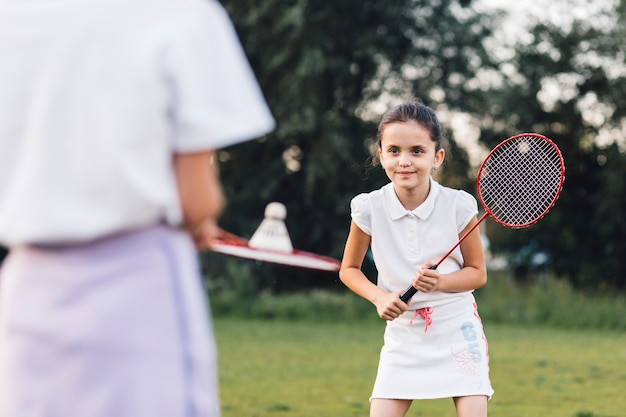 Smiling girl playing badminton with her friend Free Photo