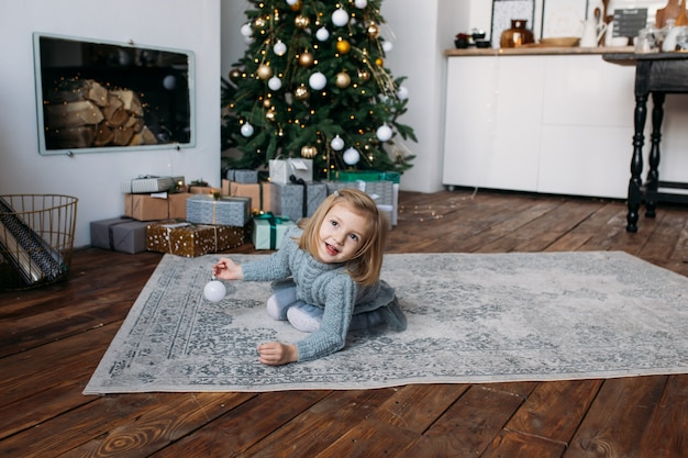 Smiling girl playing with christmas decoration Premium Photo