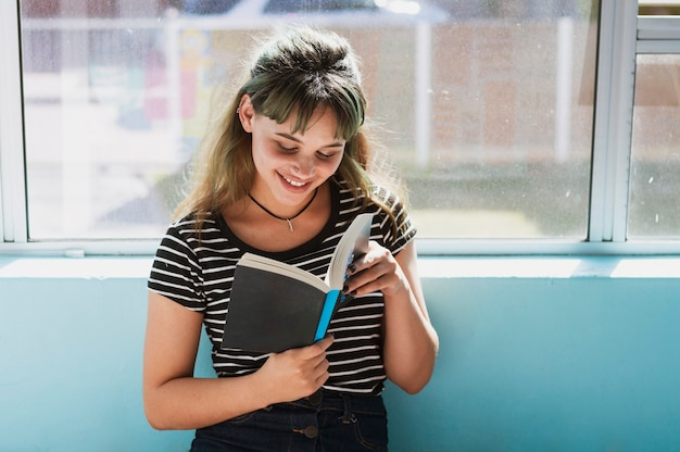 Smiling girl reading in school Free Photo