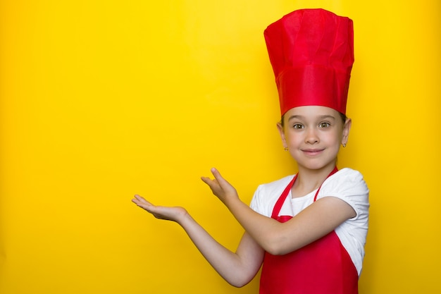 Smiling girl in a red chef's suit points with both hands to a copyspace Premium Photo