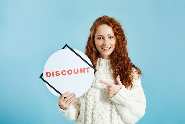 Smiling girl showing banner of sale Free Photo