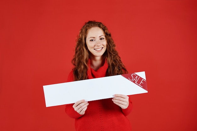 Smiling girl showing empty banner of sale Free Photo