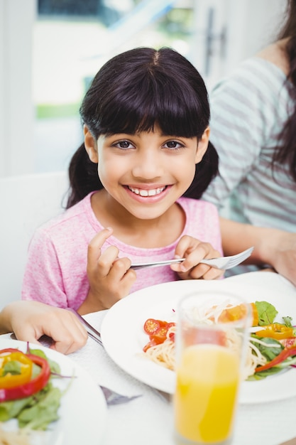 Smiling girl sitting at dining table Premium Photo