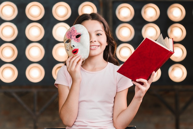 Smiling girl sitting in front of stage light holding mask and book Premium Photo