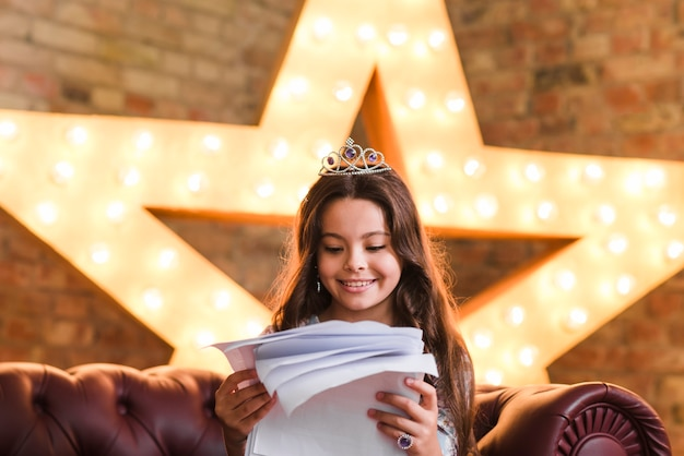 Smiling girl sitting on sofa reading scripts against glowing star in background Free Photo