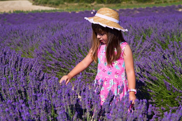 Smiling girl sniffing flowers in a lavender field Premium Photo
