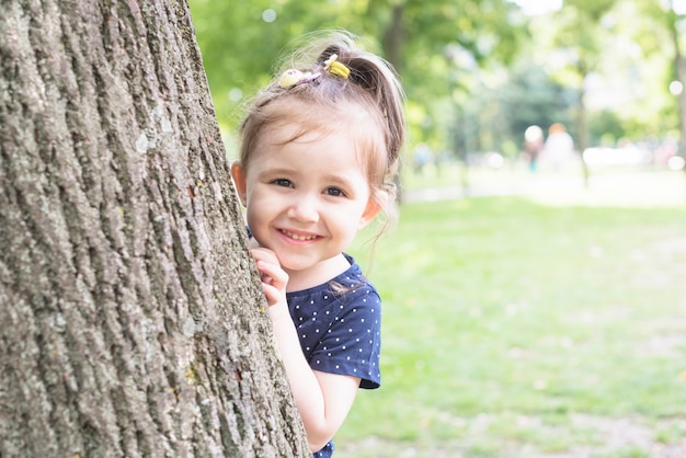 Smiling girl standing behind the tree trunk peeking in the garden Free Photo