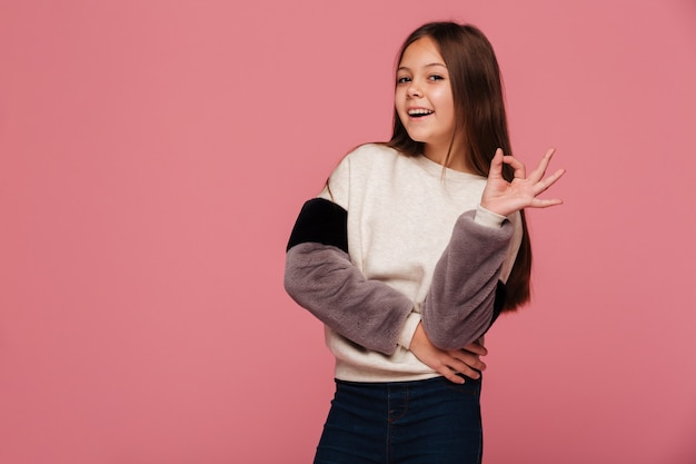 Smiling girl in sweater looking and showing ok gesture Free Photo