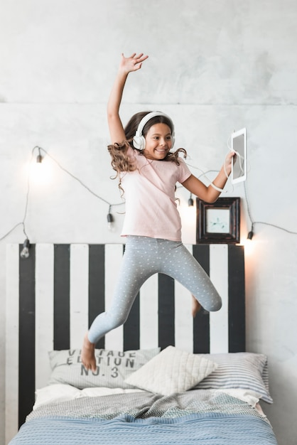 Smiling girl wearing headphone jumping over the bed with digital tablet Free Photo