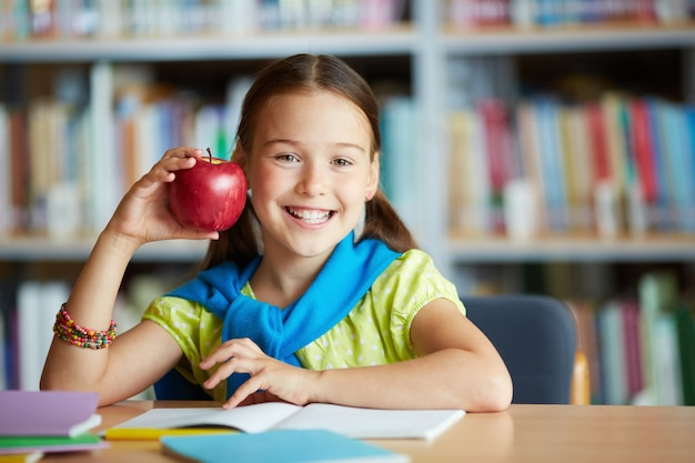 Smiling girl with an apple Free Photo