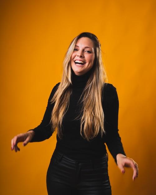 Улыбающаяся девушка со светлыми корнями, родившимися, смотрит в камеру в черной рубашке и брюках Premium Фотографии