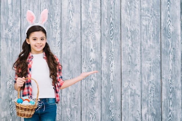 Smiling girl with bunny ears holding basket of easter eggs presenting against gray wooden desk Free Photo