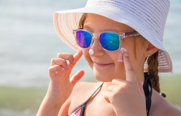 Smiling girl with hat smears protective face cream on the beach Premium Photo