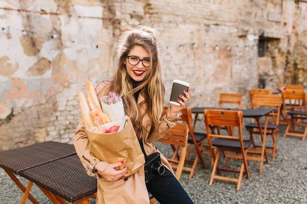 Улыбающаяся девушка с длинными вьющимися волосами держит сумку с едой с рынка и застенчиво позирует. милая молодая женщина устало прислонилась к забору после покупок. покупка продуктов, покупка еды Бесплатные Фотографии