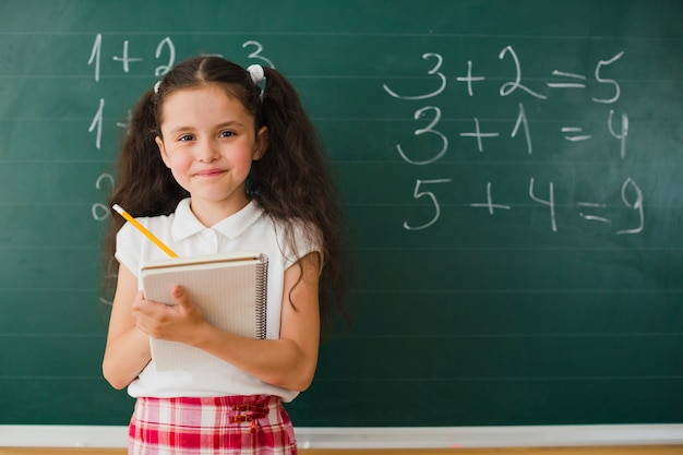 Smiling girl with notepad in class Premium Photo