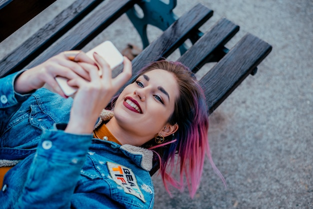 Smiling girl with purple hair lying on a bench, using phone. Premium Photo