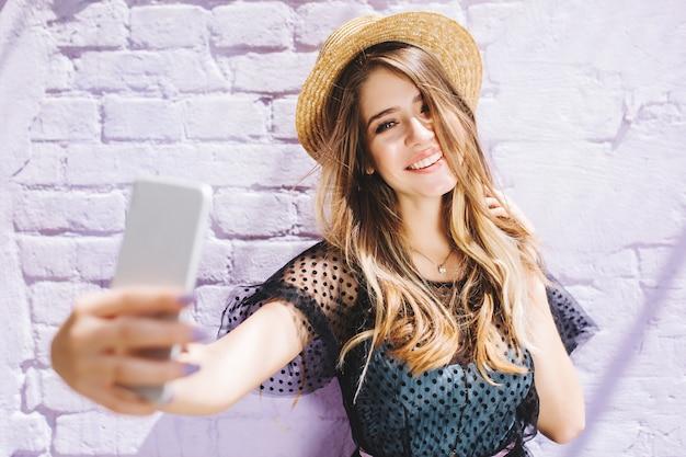 散歩中に天気の良い日を楽しんで、自分撮りを作る光沢のある髪の笑顔の女の子 無料写真