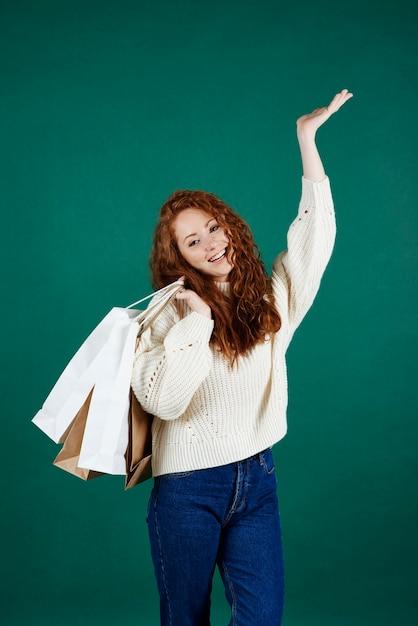 스튜디오 촬영에서 쇼핑 봉투와 함께 웃는 소녀 무료 사진
