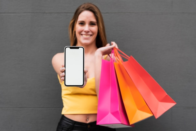 Smiling girl with shopping bags holding phone Free Photo