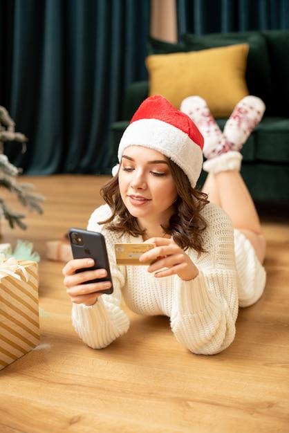 스마트 폰 및 신용 카드 크리스마스 트리 근처 웃는 소녀. 새해에 온라인 쇼핑. 그녀는 선물을 사 프리미엄 사진
