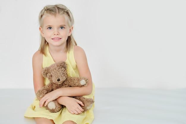 Улыбающаяся девочка с плюшевым мишкой Premium Фотографии