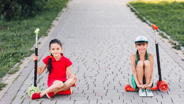Smiling girls sitting on their push scooter Free Photo