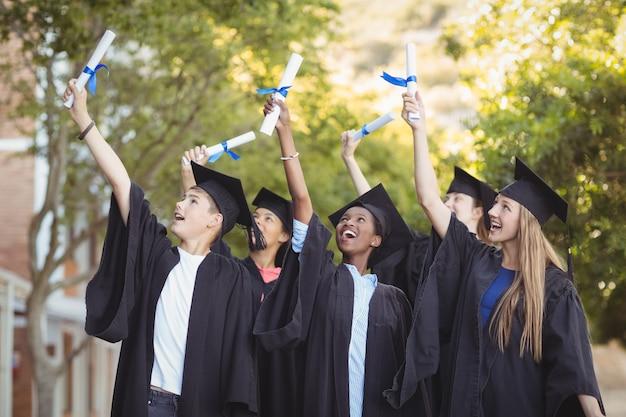Улыбающиеся аспиранты, стоящие со свитком степени в кампусе Premium Фотографии