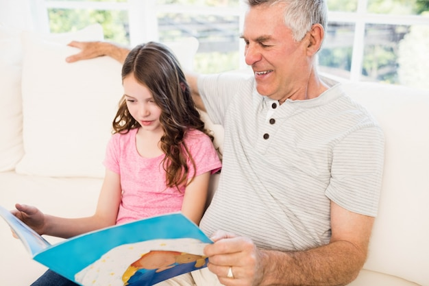 Smiling grandfather and granddaughter reading book on the sofa Premium Photo