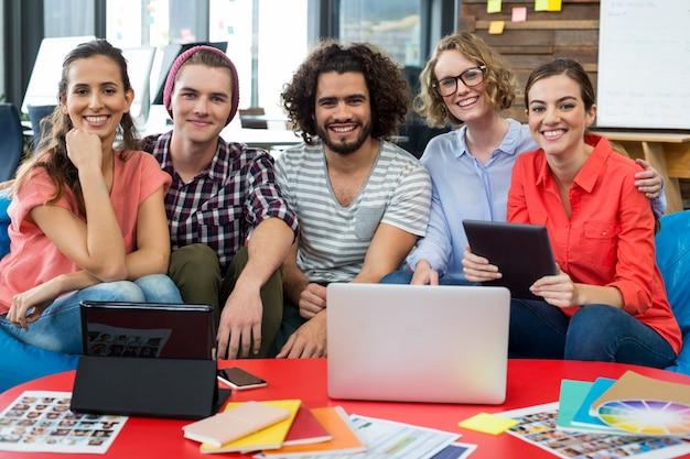 Улыбаясь графических дизайнеров, сидя в офисе с ноутбуком и цифровой планшет на столе Premium Фотографии