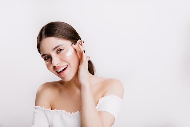 Улыбающаяся зеленоглазая девушка наносит крем на чистое лицо. брюнетка в белом топе позирует на изолированной стене. Бесплатные Фотографии